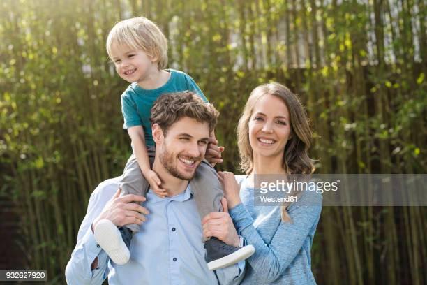 portrait of happy family in garden in front of bamboo plants - familie mit einem kind stock-fotos und bilder