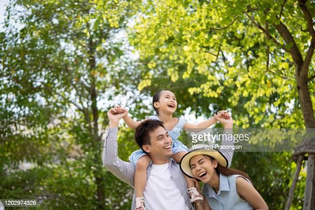 portrait of happy family in garden of their home - タイ人 ストックフォトと画像