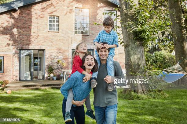 portrait of happy family in garden of their home - wohnhaus stock-fotos und bilder