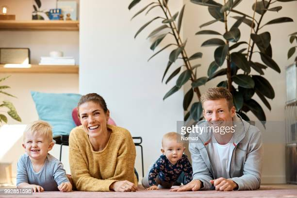 portret van gelukkige familie liggen op tapijt thuis - op de buik liggen stockfoto's en -beelden