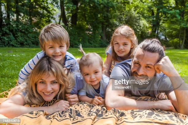 Portrait of happy family lying on meadow