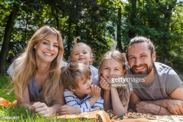 portrait of happy family lying on meadow - familie met drie kinderen stockfoto's en -beelden
