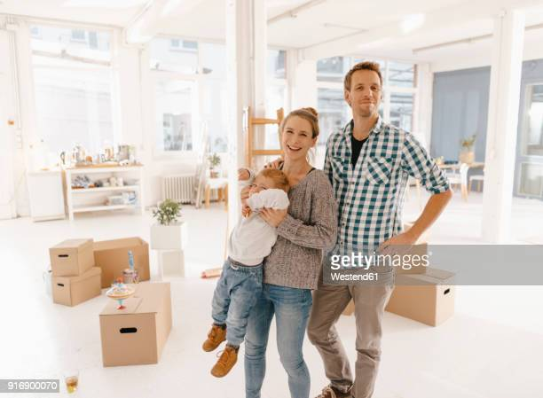 portrait of happy family moving into new home - familie mit einem kind stock-fotos und bilder