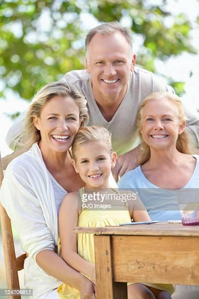 retrato de familia feliz en jardín sobre mesa de desayuno - cuatro personas fotografías e imágenes de stock