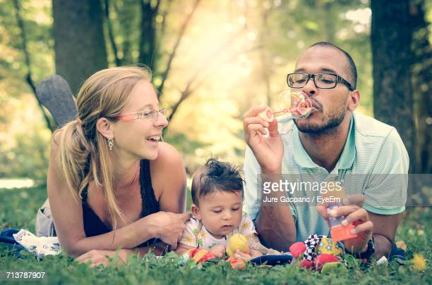 Portrait Of Happy Family Playing With Soap Bubbles