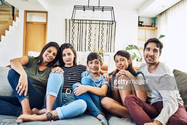 portrait of happy family relaxing on sofa at home - five people stock pictures, royalty-free photos & images