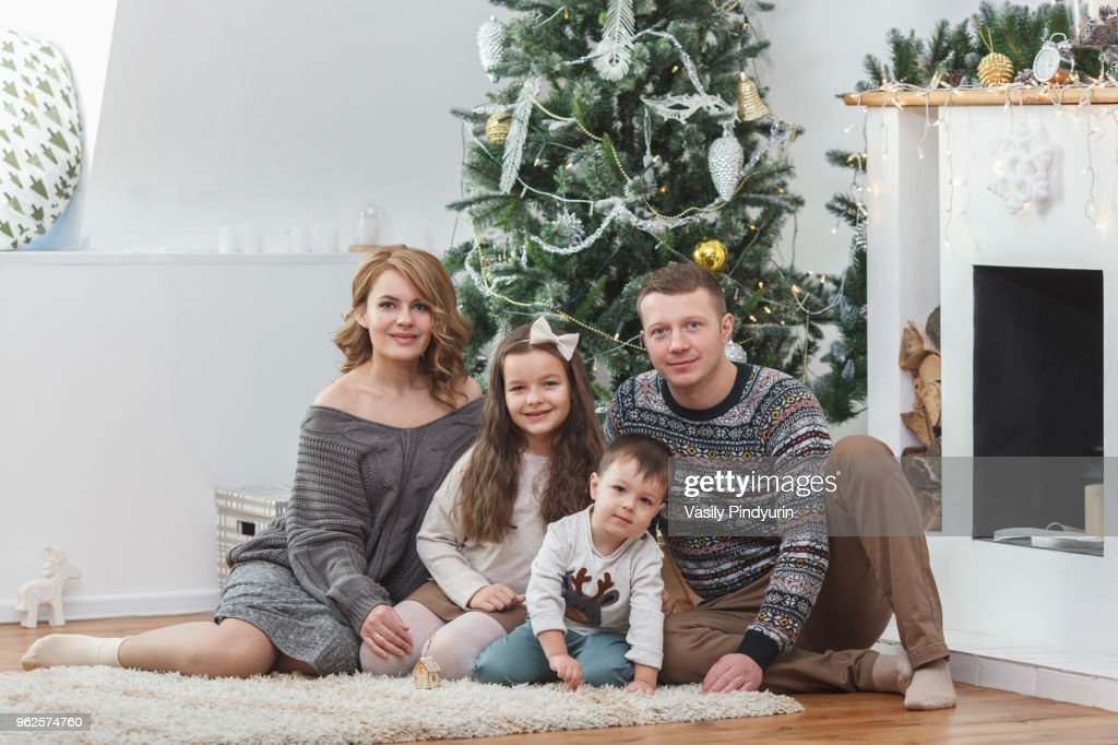 Portrait of happy family sitting against Christmas tree : Stock Photo