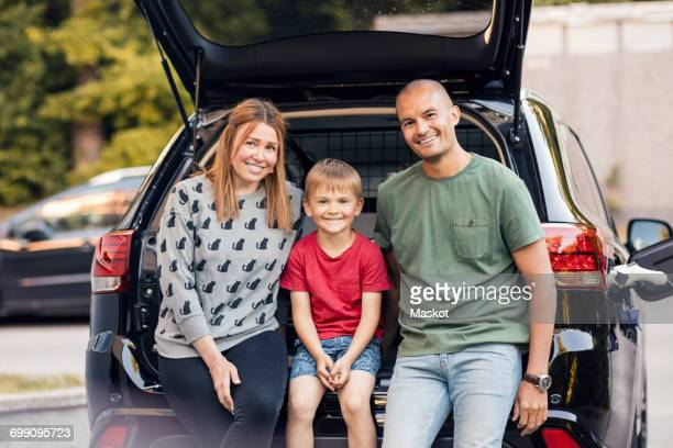 Portrait of happy family sitting in car trunk at back yard