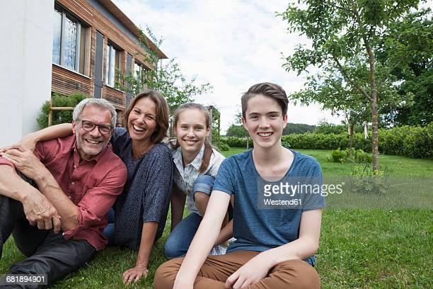 portrait of happy family sitting in garden - familie mit zwei kindern stock-fotos und bilder