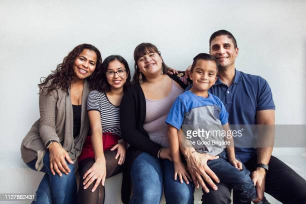 portrait of happy family sitting on bench - latino americano imagens e fotografias de stock