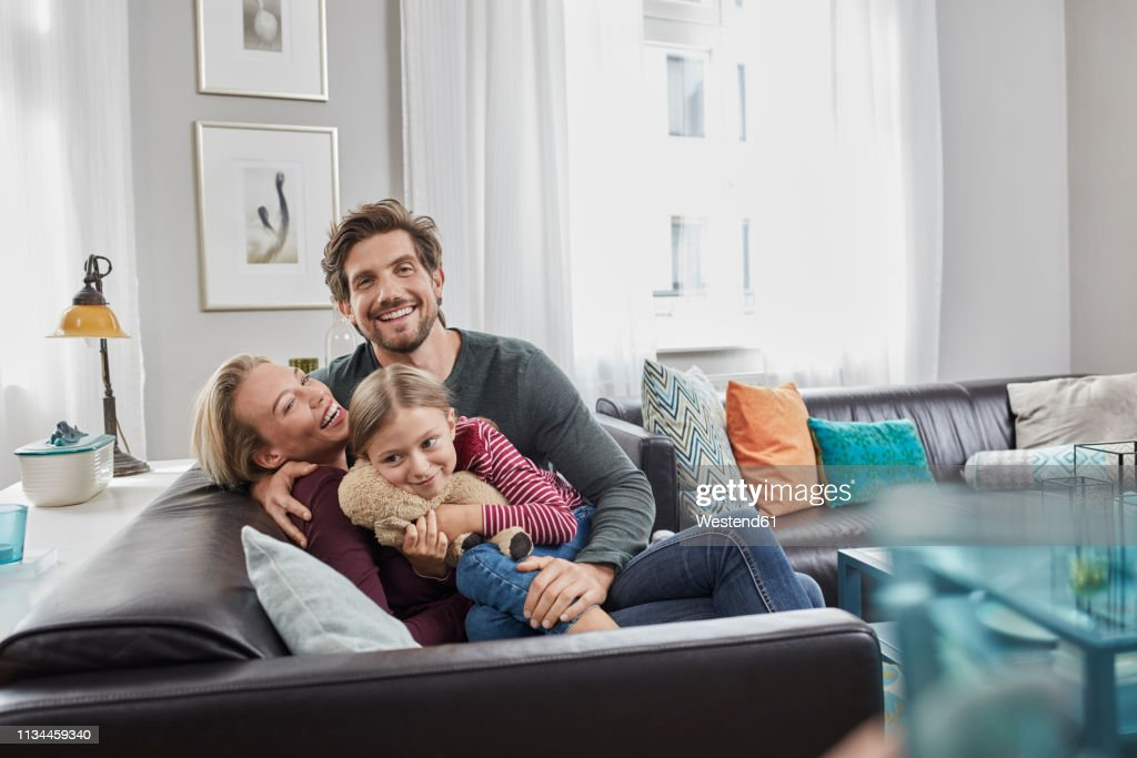 Portrait of happy family sitting on couch at home : Stock Photo