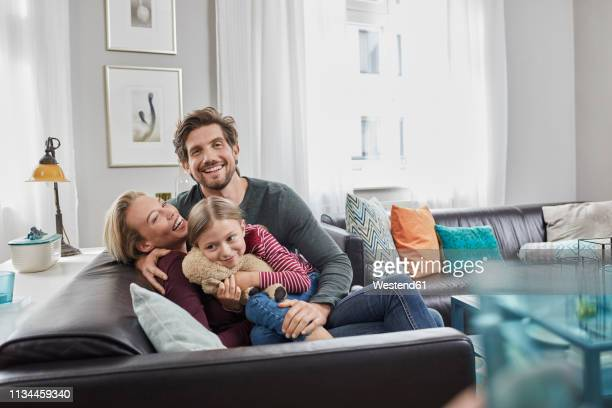 portrait of happy family sitting on couch at home - familia imagens e fotografias de stock