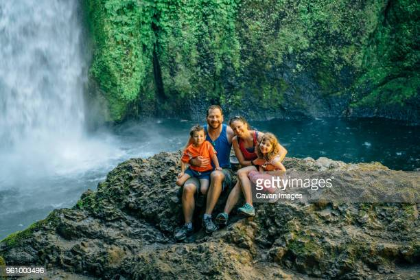 Portrait of happy family sitting on rocks against waterfall at forest