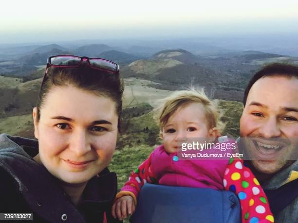 Portrait Of Happy Family Standing Against Mountains