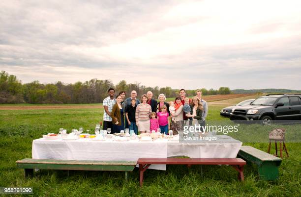 portrait of happy family standing on field during picnic - family reunion stock pictures, royalty-free photos & images
