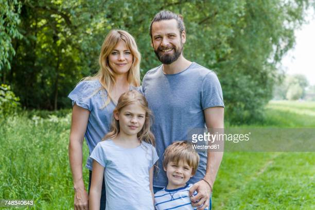 Portrait of happy family standing on meadow