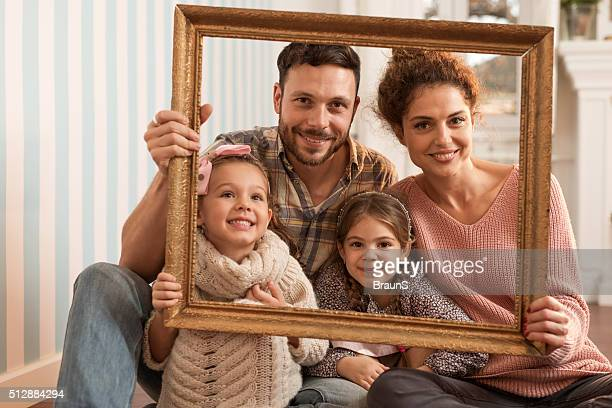 Portrait of happy family through a picture frame.