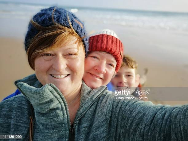 portrait of happy family wearing warm clothing at beach - real people stock pictures, royalty-free photos & images
