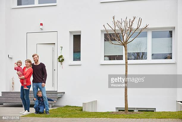 Portrait of happy family with pregnant mother in front of house