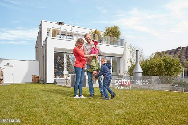 Portrait of happy family with pregnant mother in garden