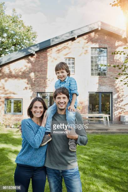Portrait of happy family with son in garden of their home