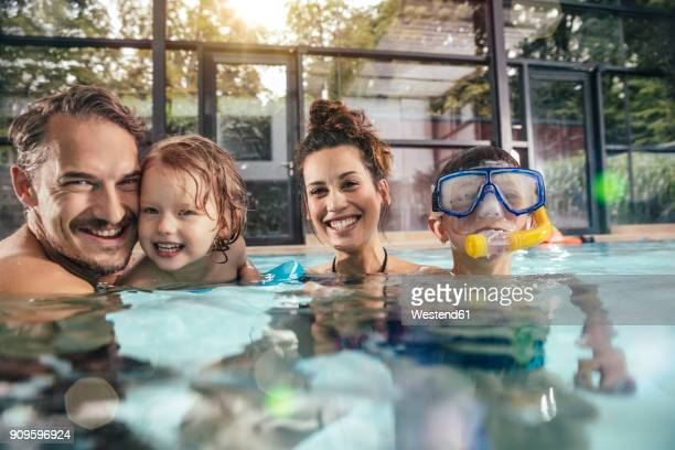 portrait of happy family with two children in indoor swimming pool - 室内プール ストックフォトと画像