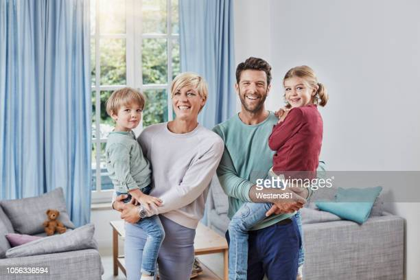 portrait of happy family with two kids at home - vier personen stock-fotos und bilder