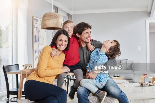 portrait of happy family with two kids at home - familie mit zwei kindern stock-fotos und bilder