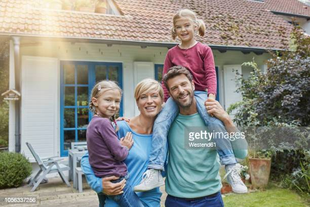 portrait of happy family with two kids in front of their home - 中流階級 ストックフォトと画像