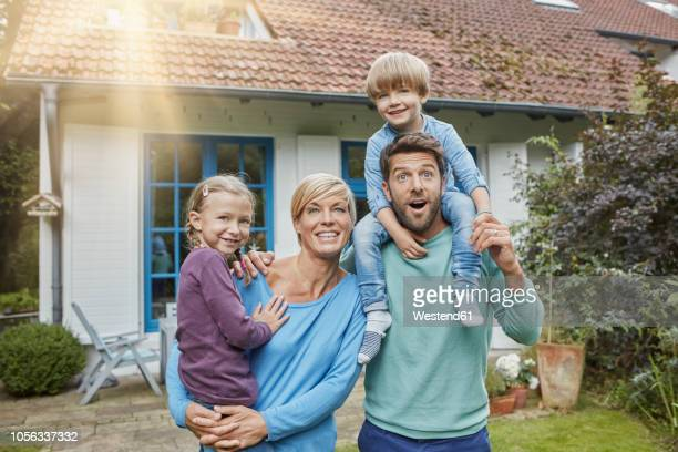 portrait of happy family with two kids in front of their home - four people stock pictures, royalty-free photos & images