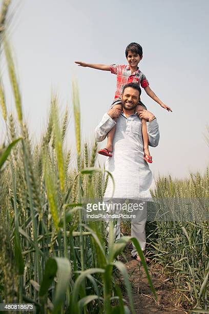 Portrait of happy farmer carrying son on shoulders at farm