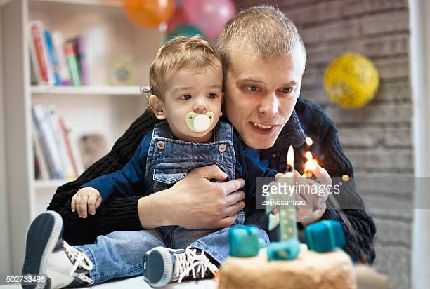 portrait of happy father and baby with birthday cake