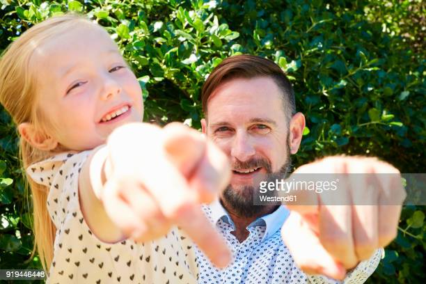 Portrait of happy father and daughter pointing their fingers