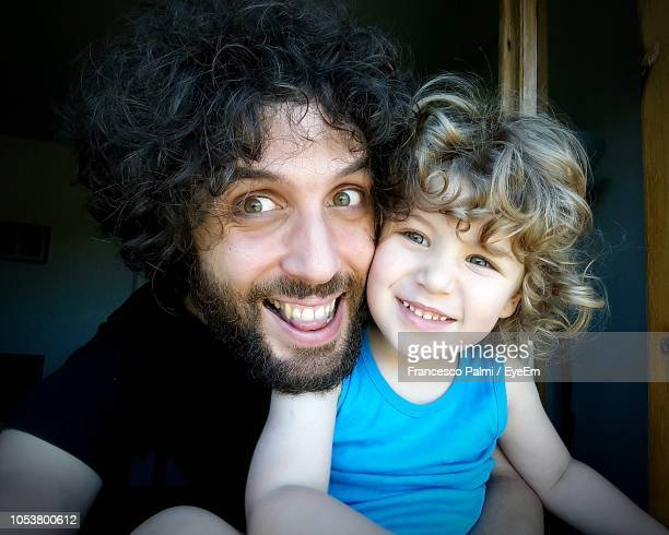 Portrait Of Happy Father And Son At Home