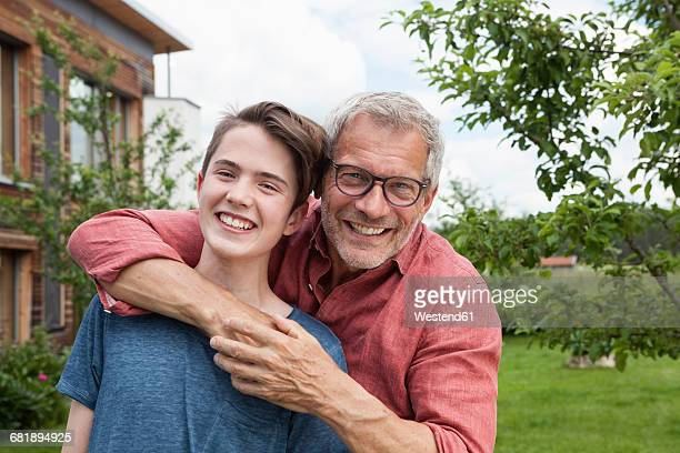 Portrait of happy father and son in garden