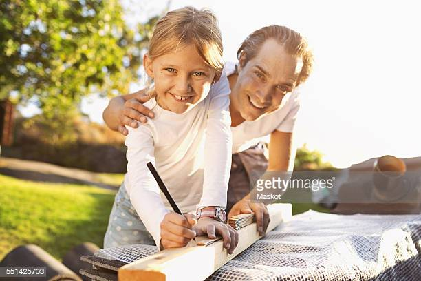 Portrait of happy father assisting daughter in measuring plank