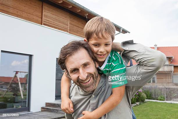 Portrait of happy father carrying son in garden