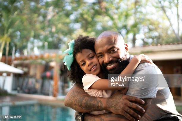 portrait of happy father hugging his daughter - fathers day stock pictures, royalty-free photos & images