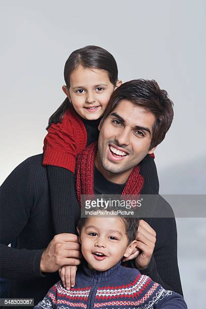 Portrait of happy father with children over grey background