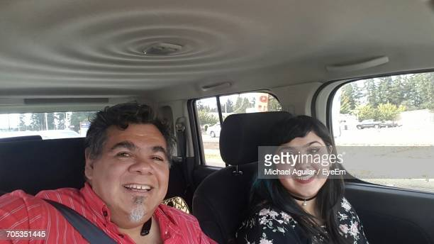 Portrait Of Happy Father With Daughter Traveling In Car