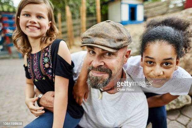 portrait of happy father with two girls outdoors - multiculturalism stock pictures, royalty-free photos & images