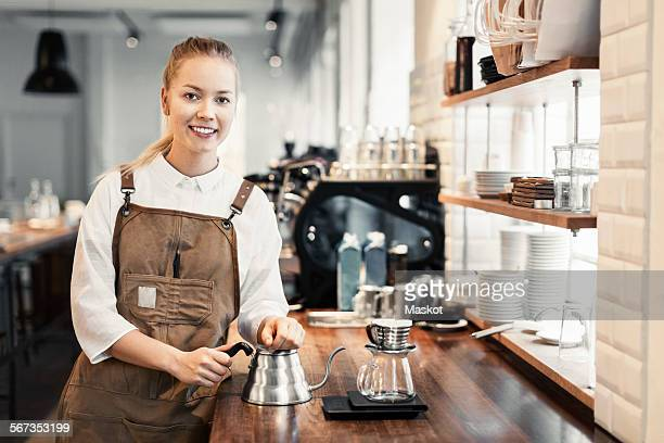 Portrait of happy female barista standing at counter in coffee shop