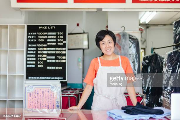 portrait of happy female dry cleaning shop owner - dry cleaner stock pictures, royalty-free photos & images