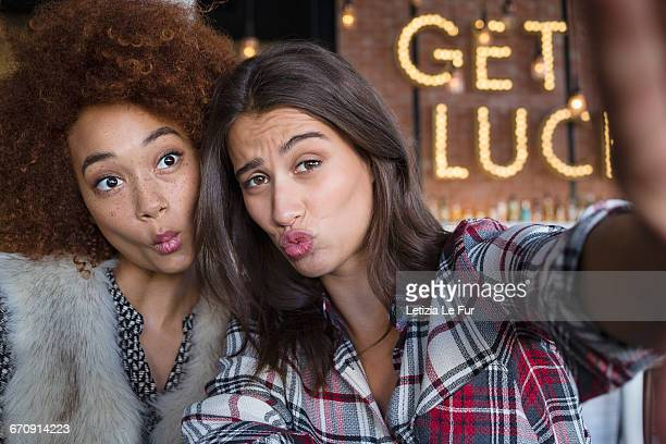 portrait of happy female friends having fun in cafe - puckering stock pictures, royalty-free photos & images