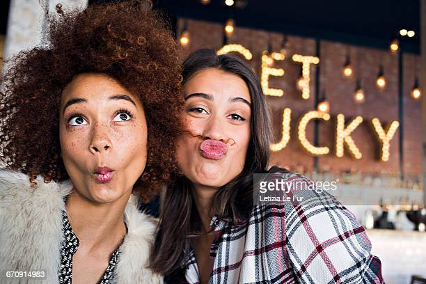 Portrait of happy female friends having fun in cafe