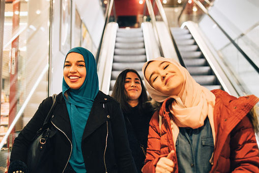 Portrait of happy female friends on escalator in shopping mall - gettyimageskorea