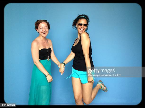 Portrait Of Happy Female Friends Standing Against Blue Background