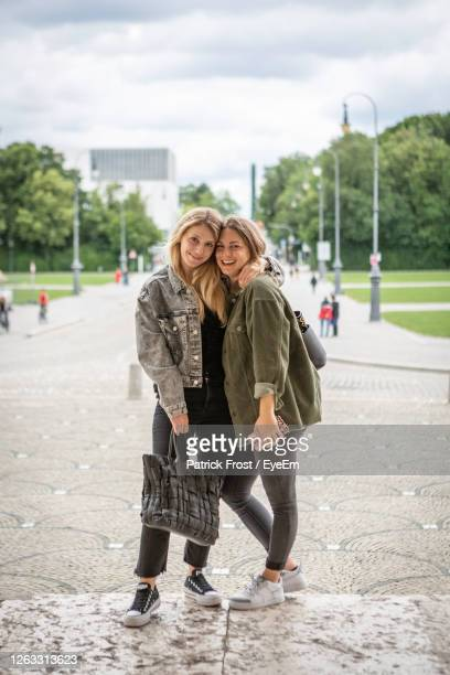 portrait of happy female friends standing on street in city - female friendship stock pictures, royalty-free photos & images