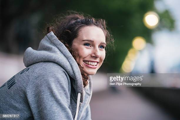 portrait of happy female runner taking a break - hooded top stock pictures, royalty-free photos & images