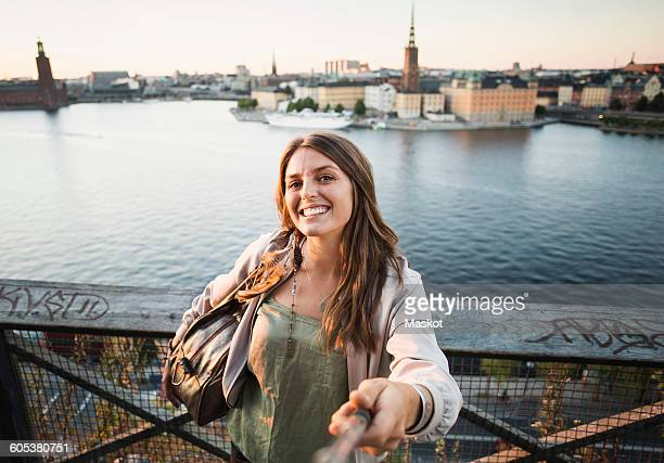 Portrait of happy female tourist holding monopod on bridge by river